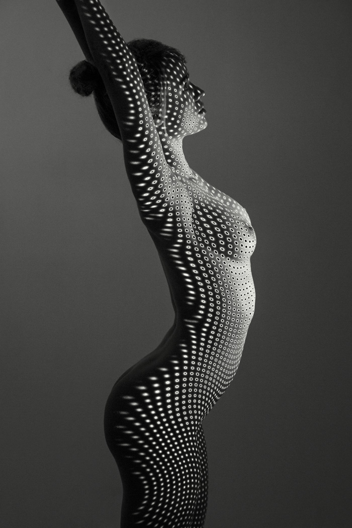 Nude B+W woman with projected dots in the studio