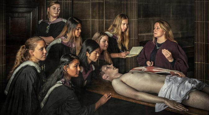 seven women medical students stand around a cadaver at an anatomy lesson